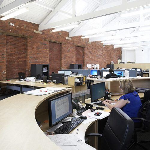 Busy working environment in festoon rooms at Sunny Bank Mills, Leeds.