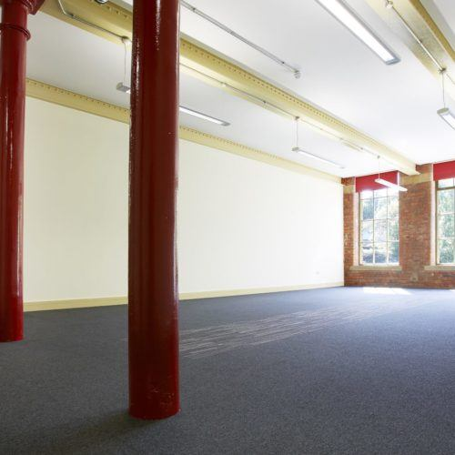 Empty business space with red pillars at Sunny Bank Mills., Leeds.